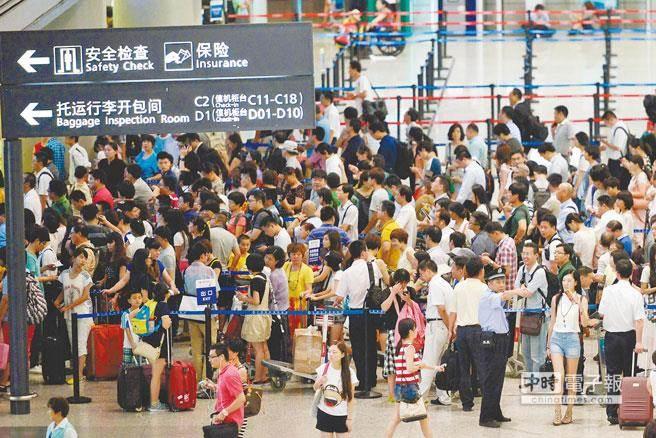 兩岸春節加班機明天上午8時開賣。圖為旅客去年春節期間在上海虹橋機場排隊換票。(臺媒取自新華社)